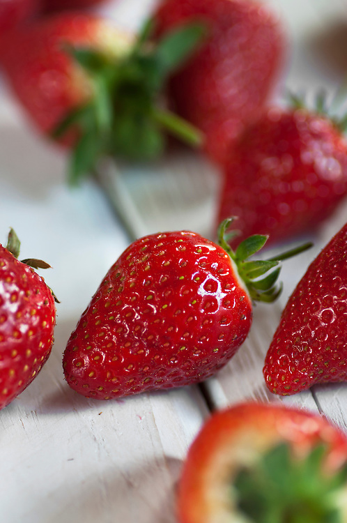 Close up of strawberries on a wooden table.