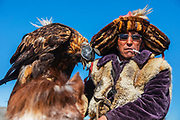 Portrait of Kazakh eagle hunter with his golden eagle (Aquila chrysaetos), Altai Mountains, Bayan Ulgii, Mongolia