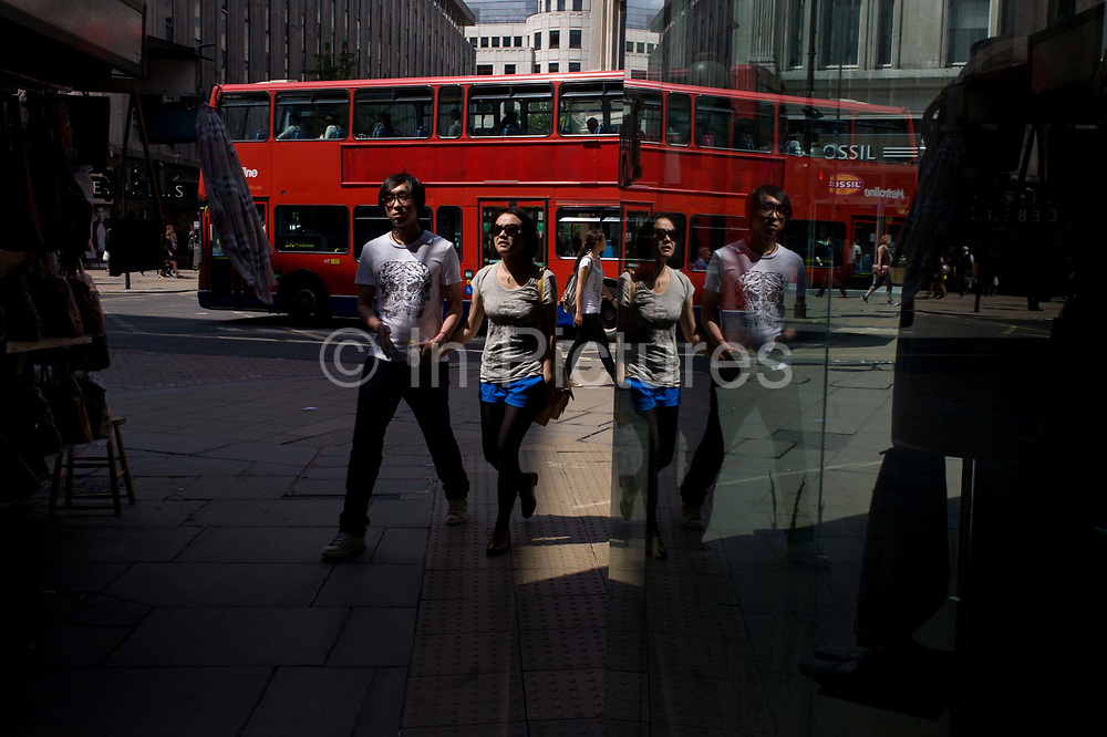 An Asian couple walk turn a sunny corner in central London.