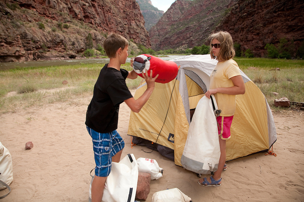 North America, United States, Colorado, Dinosaur National Monument, Green River (Gates of Lodore section), boy and girl setting up tent at campsite.  MR