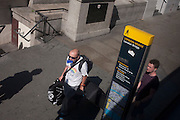 An aerial view of bus passenger holds his travel card in his mouth on Lonfon Bridge, on 13th September 2016, in the City of London, England.