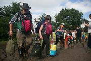 Newly arrived party people make their way through deep mud with their camping gear at the Glastonbury Festival 22th July 2016, Somerset, United Kingdom.  The Glastonbury Festival runs over 3 days and has 3000 acts, including music, art and performance and approx. 150.000 attend the anual event.