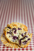 A single blueberry muffin sits on a red checkered tablecloth.