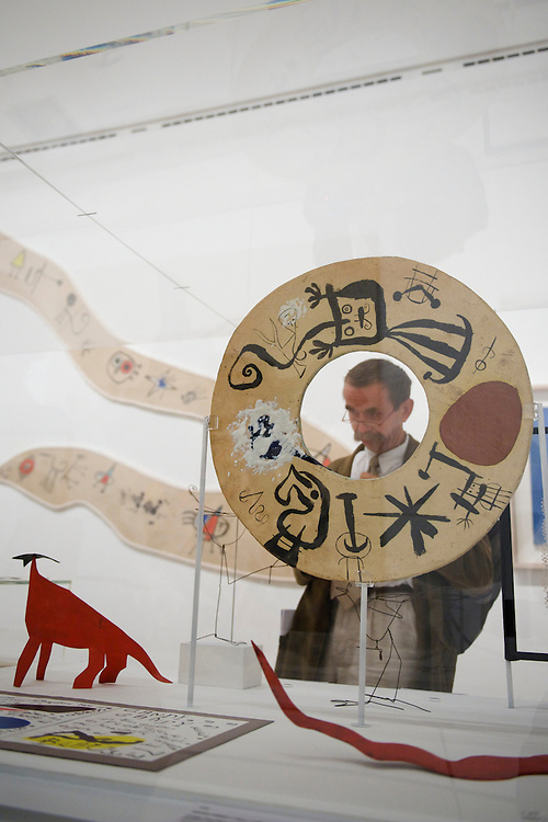 London.  September 30, 2008.  A museum goer admires a Joan Miro sculpture, 'Large double-sided Disc,' part of the Miro, Calder, Giacometti, Braque exhibition at the Royal Academy of Arts.  The show opens on October 4 and runs until January 2, 2009.