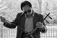 """China, Beijing, 2008. Along the Temple of Heaven's long covered walkways, a musician plays his """"erhu,"""" one of China's most evocative instruments.."""