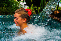 A woman relaxing in the outdoor vitality pool at the Spa in the Four Seasons Resort Bora Bora, French Polynesia.