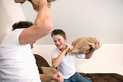 Father and son having pillow fight in living room