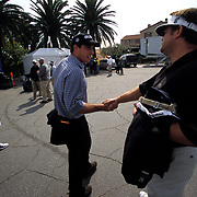 """Called """"The Swoop"""" by caddies in search of work, Billy Zimmerman, right, greets PGA Tour player Matt Gogel in the parking lot at Riviera CC in Los Angeles in front of Gogel's caddy, at left. Word had spread that Gogel was """"in play"""" and looking for a new caddy. Dan McQuilkin, left,  was hoping to turn a temporary job as Gogel's caddy into a permanent one. With caddies earning 5-10% of a tour player's winnings, competition is fierce for proven winners like Gogel."""
