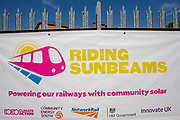 The Riding Sunbeams banner at the array of solar panels next to the line near Aldershot Railway Station.  This innovative project is the first in the UK to power the railway with electricity generated from solar power and, if successful, could see many Network Rail sites across the country adapting this sustainable energy approach. Riding Sunbeams is a social enterprise, run by 10:10 Climate Action. Built with Community Energy South and partnered with Network Rail and The Department for Transport and by InnovateUK.  Aldershot, Hampshire, United Kingdom. Riding Sunbeams is a world leading project to connect solar panels directly into electrified rail routes to power the trains. Direct supply of solar power to rail traction systems has never been done. But it has huge potential - from metros, trams and railways in the UK and around the world.<br /> (photo by Andy Aitchison / 1010 Climate Action)