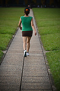 A woman is training after work in front of Ho Chi Minh mausoleum in Hanoi. We see her from behind, walking a path between patches of grass. She has a pony tail and wears an outfit for sport, little black shorts, green tight top, running shoes. Her silhouette and the path creates a perspective.