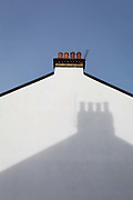 The shadow of a neighbours chimney on the side of an end-of-terrace house in south London, on 29th January 2019, in Herne Hill, Lambeth, London, England.