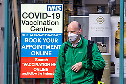 Licensed to London News Pictures. 21/10/2021. London, UK. Members of the public walk past a Covid-19 vaccination Centre in Fulham, south-west London this morning as the British Medical Council accused the government of neglect for not implementing Covid-19 rules such as mandatory face masks and work from home. Yesterday, Health Secretary Sajid Javid predicted new infections could rise to 100,000 a day this winter and urged eligible members of the public to get their booster jabs as soon as possible. Photo credit: Alex Lentati/LNP