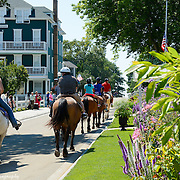 A Trail Guide Leads Her Customers And Horses Past The Windsor Building On Mackinac Island, Michigan