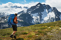 Adult male backpacker hiking on Red Face Mountain, Challenger and Whatcom Peaks are in the background, North Cascades National Park