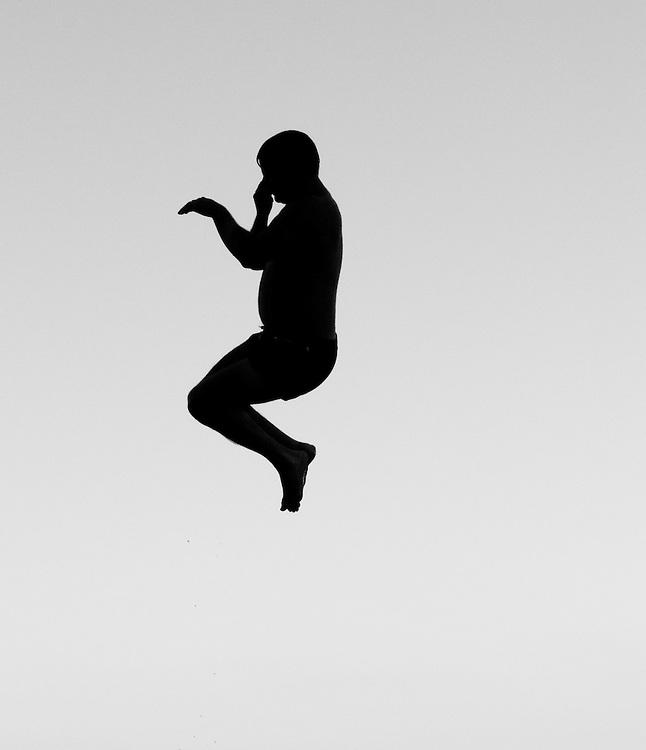 My friend Jonathan in mid-air having jumped off a rope swing into Lake Washington at Magnuson Park, Seattle, Washington.