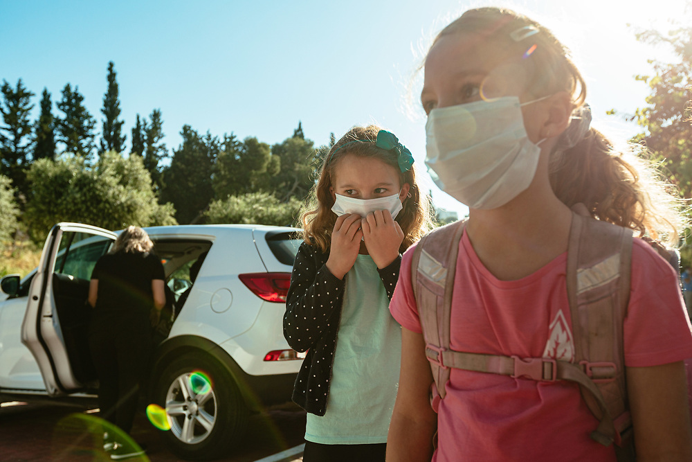 Twin girls Alma (C) and Clil Michel (R) wearing protective face masks, are seen as they await their turn to enter the elementary school where the girls study, in Jerusalem, Israel, on May 3, 2020.