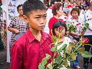 17 FEBRUARY 2013 - BANGKOK, THAILAND:  A boy wearing red holds a red rose while he waits to greet Thai Prime Minister Yingluck Shinawatra during a rally for Pongsapat Pongchareon. Pol General Pongsapat Pongcharoen, a former deputy national police chief who also served as secretary-general of the Narcotics Control Board is the Pheu Thai Party candidate in the upcoming Bangkok governor's election. Yingluck is the head of the party and campaigning with Pongsapat, who resigned from the police force to run for Governor. Former Prime Minister Thaksin Shinawatra reportedly recruited Pongsapat. Most of Thailand's reputable polls have reported that Pongsapat is leading in the race and likely to defeat Sukhumbhand Paribatra, the Thai Democrats' candidate and incumbent. The loss of Bangkok would be a serious blow to the Democrats, whose base is the Bangkok area.     PHOTO BY JACK KURTZ