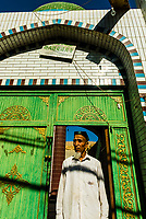 A Uyghur man stands outside a small mosque in Grape Valley outside Turpan, Xinjiang Province, China.