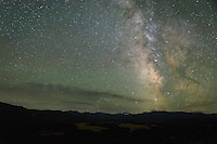 The milky way shines brightly above Black Tooth Mountain while airglow gives a green tint to the sky.