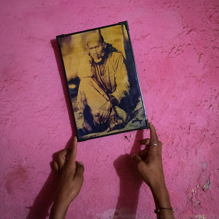 A old picture portrait of Sai Baba, an Indian spiritual master. Pink wall.