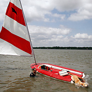 """Kurt Fineis, of Beaufort, pulls his bonito sailboat towards the Pigeon Point dock as his pet lab named Maizy makes a dive for shore after being towed from the Beaufort River area by a local boater on August 24, 2014. """"The current was just crazy..."""" said Fineis.  The National Weather Service announced a Rip Current Statement in effect from August 24, 03:05 PM EDT until August 25, 08:00 PM EDT."""