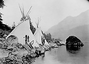 Three Native American men, probably Umatilla, stand on shore of river next to tepees. c1922.  Photograph by Ralph Irving Gifford (1894-1947).