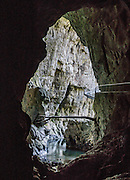 """A log was left suspended high in Mahorcic Cave (Mahorciceva jama) by the Reka River in Slovenia. The wonderful self-guided Part 2 of Skocjan Caves walking tour follows the mysterious Reka River from Mala Dolina (Small Doline, a sinkhole) through Mahorcic Cave (Mahorciceva jama) upstream underground for 350 meters over exciting bridges and dimly lit passages. From a large-scale karst drainage, the Reka River has carved and dissolved dramatic subterranean passages through limestone over several million years. Karst topography is a geologic formation of dissolving bedrock. Our word for """"karst"""" likely evolved from the Slovene noun kras and earlier proper noun Grast, referring to Slovenia's Karst Plateau. Visit Skocjan Caves (Skocjanske jame) Regional Park near Divaca, in the Littoral region of the Republic of Slovenia, Europe. UNESCO has honored Skocjan Caves as a World Heritage Site."""