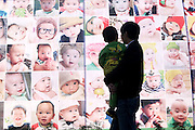 BEIJING, CHINA - MARCH 03: (CHINA OUT) <br /> <br /> China To End One-Child Policy<br /> <br /> A man walks pass a poster printed with babaies\' faces with his daughter on November 17, 2013 in Taizhou, Zhejiang Province of China. China has decided to abandon its 35-year-old one-child policy, allowing all couples to have two children, the Communist Party of China (CPC) announced after a key meeting on Thursday.©Exclusivepix Media