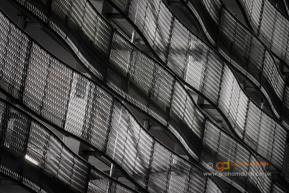 An abstract view of a building exterior in Sheffield. Captured at night, the interior lights give a glow to, and accentuate the form of, the wonderfully curved metal panels. An urban scene in South Yorkshire, England, UK.