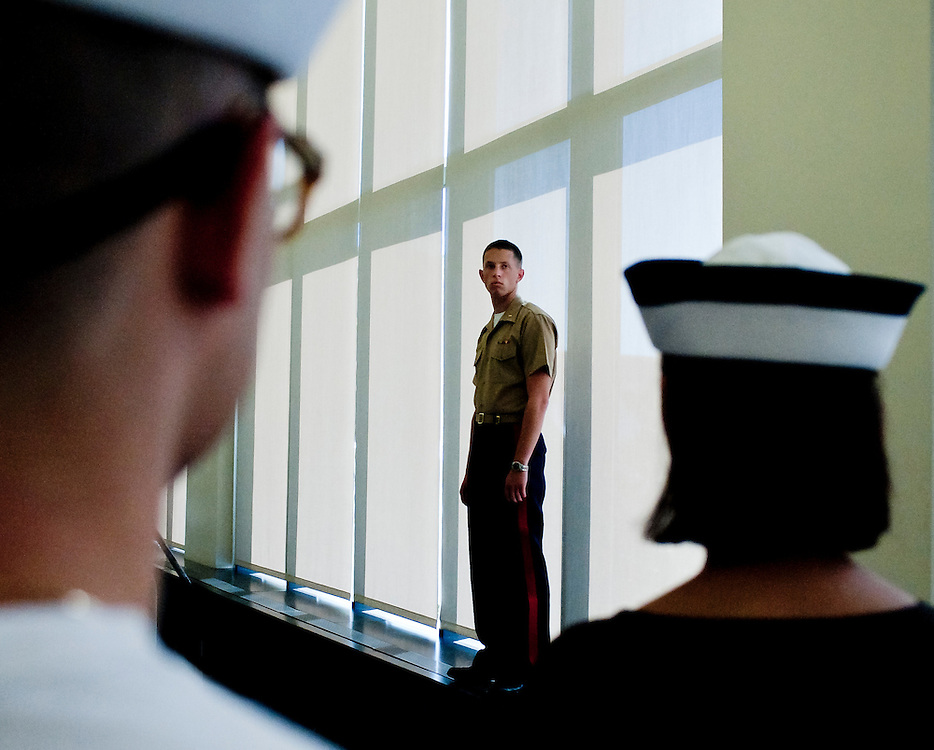 """A United States Marine oversees some of the freshmen as they are processed on their first day at the U.S. Naval Academy in Annapolis, MD. Approximately 1,230 young men and women arrived at the U.S. Naval Academy's Alumni Hall, Thursday, July 1, for Induction Day to begin their new lives as """"plebes"""" or midshipmen fourth class (freshmen). """"I-Day"""" culminates when the members of the Class of 2014 take the oath of office at a ceremony at 6 p.m. in Tecumseh Court, the historic courtyard of the Bancroft Hall dormitory. Over 17,400 young men and women applied to be members of the Naval Academy Class of 2014 - a record for USNA."""