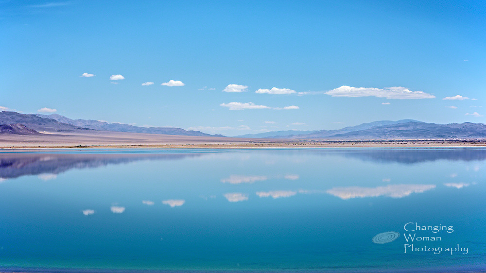 The glassy surface of Walker Lake, north of Hawthorne, NV, reflects the surrounding mountains and cotton-ball clouds scattered across the blue sky: the peaceful face of Walker Lake.