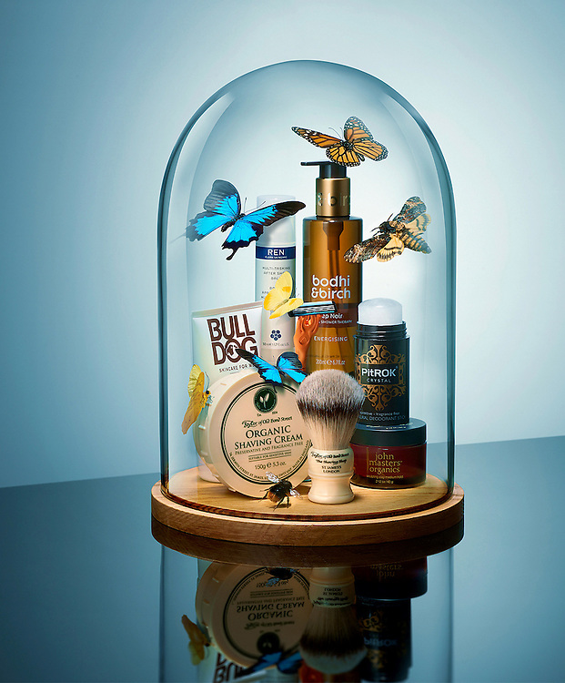 Mens Cosmetics under a glass dome with bugs.