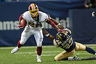 Washington Redskins running back Clinton Portis (L) gets dragged down by St. Louis Rams Ron Bartell (R) in the first quarter, during the Redskins 24-9 win at the Edward Jones Dome in St. Louis, Missouri, December 4, 2005.