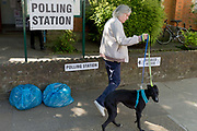 On the morning of the European Elections in the UK, a local   woman walks her dog past the Polling Station at the Baptist Church in East Dulwich. Barnabas Parish Hall in Dulwich Village, on 23rd May 2019, in south London, England UK.