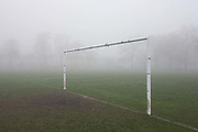 London park goalpost on an early misty morning. Football is off, cancelled due to bad weather but the remnants of the last game has been left by the frozen muddy goalmouth. In the distance are the misty forms of 100 year-old ash trees and the hazy presence of Edwardian residential homes.