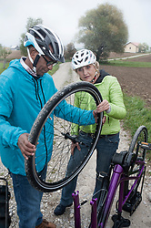 Senior couple adjusting wheel of cycle on dirt road, Bavaria, Germany