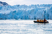Adventure cruise passengers on a rubber zodiac dingy tour an iceberg in Spitsbergen, Norway in July