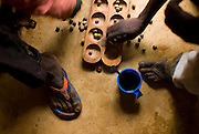 Young men playing a mancala game, typical to Africa where is know by many names as  Wari, Awele, Awélé, Aualé, Ouri, Aware.