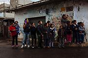 Un grupo de jóvenes y niñas esperan a que aparezcan los Xinacates enmascarados y pintados del cuerpo con aceite vegetal y pigmento durante el carnaval de san Nicolás de los Ranchos.