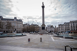 © Licensed to London News Pictures. 20/03/2020. London 09.42, UK. A man stands in the middle of a deserted Trafalgar Square on the first day of Spring which would normally be teaming with tourists and workers now resembles a ghost town as the Coronavirus crisis continues. Photo credit: Alex Lentati/LNP