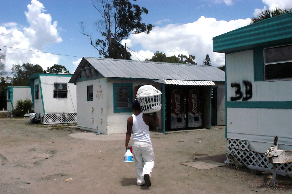 A migrant farm worker walks through the trailer camps where majority of  them live in  Immokalee, FL, Apr. 16, 2003.