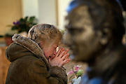 Moscow, Russia, 02/04/2005..As Pope John Paul ll lies close to death in the Vatican, Russian Catholics pray for him inside the Cathedral of the Virgin Mary's Immaculate Conception, Russia's largest Roman Catholic church. A woman weeps as she prays beside a bust of Pope John Paul ll.