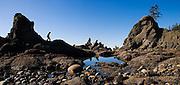 Zach Podell-Eberhardt climbs over rocks along the rugged coastline at Shi Shi Beach, Olympic National Park, Washington.