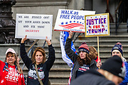 """Sandra Weyer (second from left) and Pauline Bauer (third from left) hold signs during a """"Stop the Steal"""" rally in Harrisburg, Pennsylvania on January 5, 2021. Supporters of President Donald Trump urged legislators to decertify the election during the rally at the Pennsylvania State Capitol. (Photo by Paul Weaver)"""