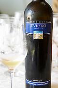 Wine glasses in the tasting room. Bottle of Tvrtko Vrhunsko Suho Vino white wine. Detail of label with a picture of a monument and vineyard. Vinarija Citluk winery in Citluk near Mostar, part of Hercegovina Vino, Mostar. Federation Bosne i Hercegovine. Bosnia Herzegovina, Europe.
