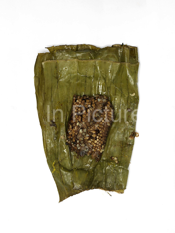 Bee larvae collected from the forest, cooked in a banana leaf and sold at the roadside market in the Tai Dam village of Ban Na Mor, Oudomxay province, Lao PDR. In the past the bulk of products collected or caught from the wild were used for family consumption, but nowadays a substantial proportion of products are sold in the markets for cash. Ban Na Mor market is ideally situated on route 13 which goes to the border with China allowing them to take advantage of the many Chinese tour buses and businessmen passing through.