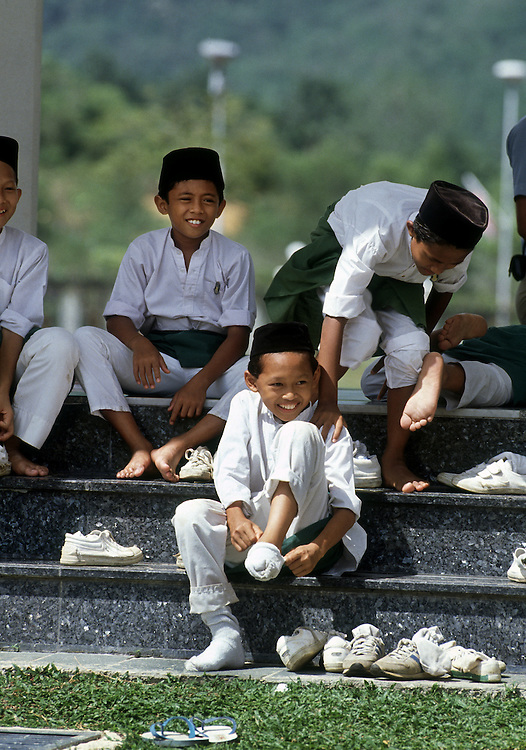 Boys take thier shoes off as they visit the Abdul Aziz Shah Mosque at Shah Alam,Kuala Lumpur,Malaysia.1989