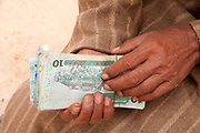 Merlin in Tunisia. Shousha camp for migrant workers displaced from Libya February to May 2011. Money changer with Libyan notes.