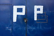 White painted letter Ps on blue gates warning of constant parking in south London. The DIY Do-it-Yourself effort is effective and noticeable so that motorists don't leave their vehicles outside blocking the entrance to the urban property. In the very middle of the landscape is a padlock, securing steel doors together.