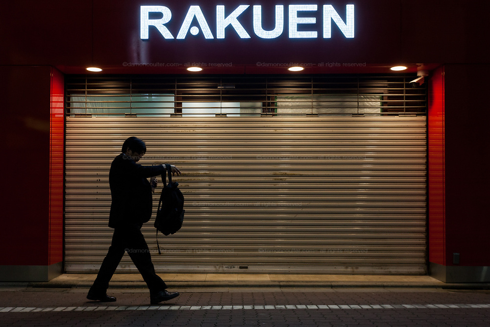 A salaryman (in silhouette) walks past a shuttered Pachinko parlour as he adjusts his backpack. Shibuya, Tokyo, Japan. Friday May 22nd 2020